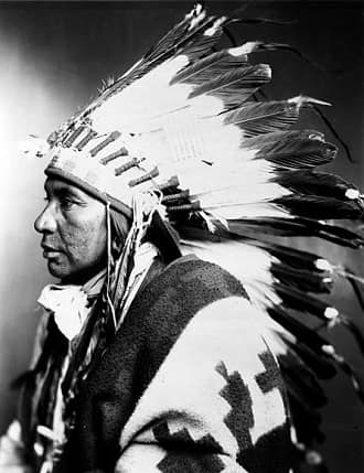 Shoshone Indian wearing war bonnet